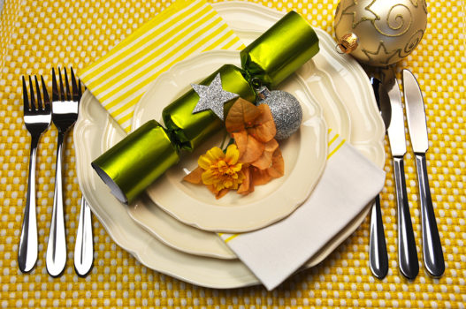 Yellow Christmas holiday table setting with plates, cutlery, baubles, Christmas cracker bon bons decorations, in a yellow theme.