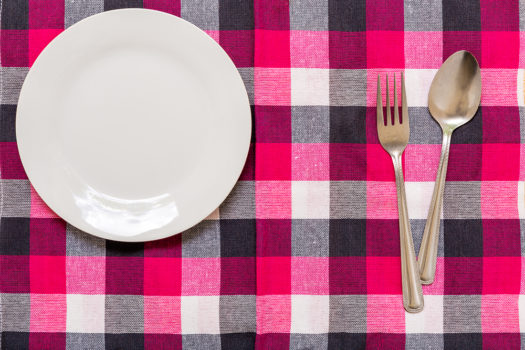 Empty plate with spoon and fork on table background.