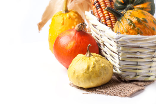 Autumn mini pumpkins and corn in basket over white