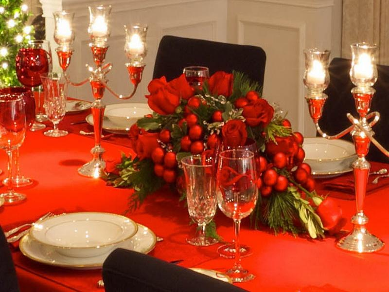 Table decorated with beautiful bright red spun polyester tablecloths and floral arrangements. Above the table can be seen beautiful candle chandeliers accompanied with other cutlery.