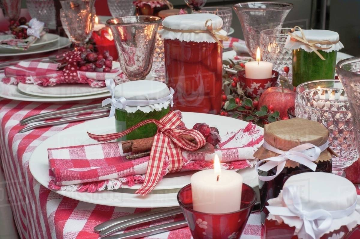 Christmas table adorned with polyester checked tablecloths and matching napkins. Included is also silverware and lit elegant holiday candles in bright red and leafy green.